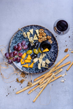 Cheese plate appetizer for party, cheese assortment platter with grapes, honey and nuts, flat lay. Grey concrete background.