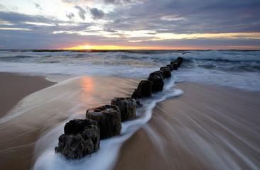 Morze Bałtyckie,wschód słońca,falochron na plaży w Kołobrzegu,Polska.
