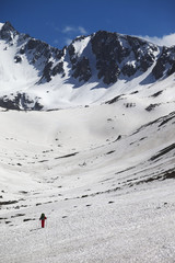 Wall Mural - Hiker in high snowy mountains at nice spring day
