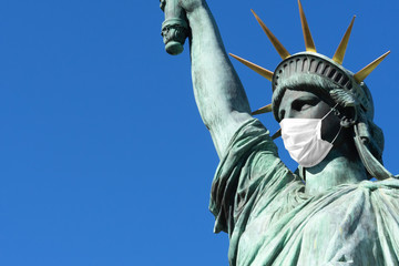 Statue of Liberty in a medical mask. Concept - pandemic in the USA ,. Statue of Liberty on the background of blue sky. Concept - quarantine in New York. Place for an inscription. Epidemic in America.