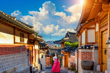 Wall Mural - Beautiful girl wearing Korean traditional hanbok at Bukchon Hanok Village. Traditional Korean style architecture in Seoul,Korea.