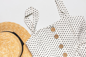 Summer women's white dress in black peas with natural wooden buttons and straw hat on light gray...