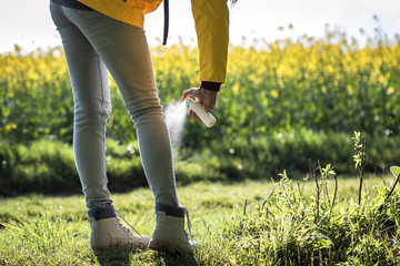Tourist spraying insect repellent on her legs and boots. Protection against tick outdoors