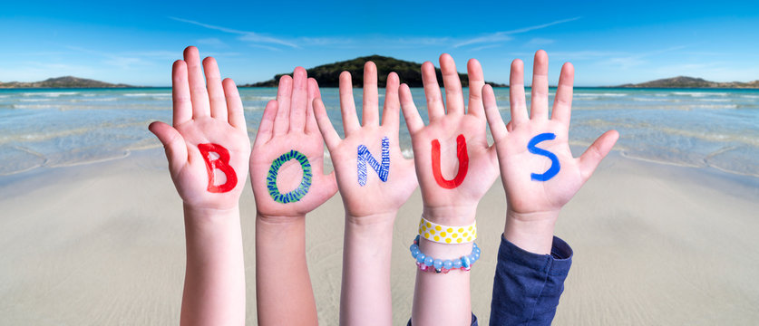 Children Hands Building Colorful Word Bonus. Ocean And Beach As Background