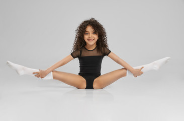 Young female gymnast demonstrating flexibility.