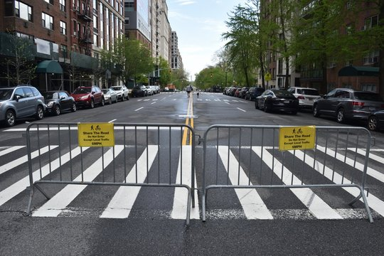 Two grey metal barricades on a crosswalk with two yellow signs reading Share The Road Do Not Enter Except Local Traffic 5MPH and pedestrian and cyclist symbols, May 3, 2020, in New York.
