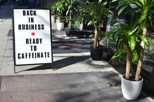 White A-frame sign reading Back In Business Ready To Caffeinate on a city sidewalk outside a coffee shop with green potted plants on a sunny day, May 7, 2020, in New York.