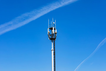 Telecommunications tower with 4G, 5G transmitters. cellular base station with transmitting antennas on a telecommunications tower against the blue sky