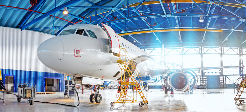 Panoramic view of aerospace hangar, civil aviation aircraft, repair and maintenance of mechanical parts in an industrial workshop.