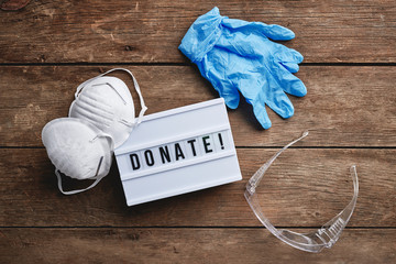 "a sign that reads, ""donate"", surrounded by masks, gloves, and protective glasses."