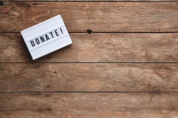 a donate sign on a wood table with copy space