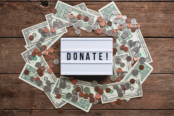 "a sign that reads, ""donate!"", surrounded by money."