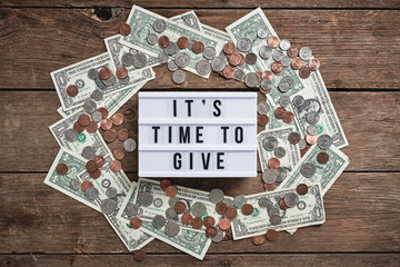 "a sign that reads, ""it's time to give"" surrounded by money."
