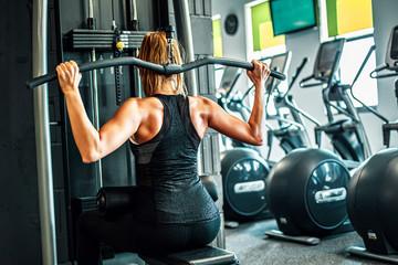 Fototapeta Kobieta trenująca na siłowni, mięśnie pleców.  obraz
