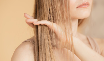 Hair care, blonde girl puts oil on her head removes dryness and brittleness