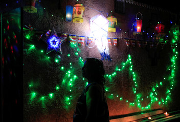 A woman watches her house, decorated with lights and lanterns, on the Vesak Day, which is celebrated in Sri Lanka on May 7th and 8th to commemorate the birth, enlightenment and death of Buddha, during the curfew amid concerns about the spread of the corona