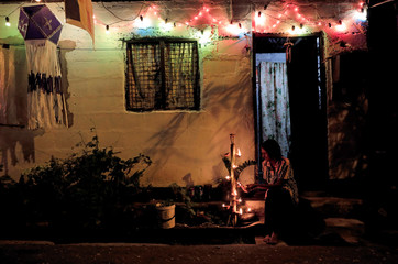 A woman lights oil lamps in front of her house decorated with lights and lanterns on the Vesak Day, which is celebrated in Sri Lanka on May 7th and 8th to commemorate the birth, enlightenment and death of Buddha, during the curfew amid concerns about the s