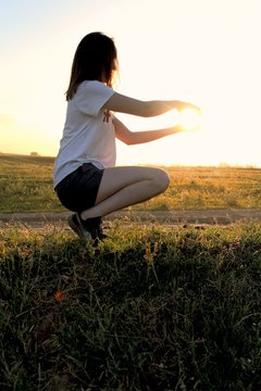 Optical Illusion Of Woman Holding Sun While Crouching On Grassy Field
