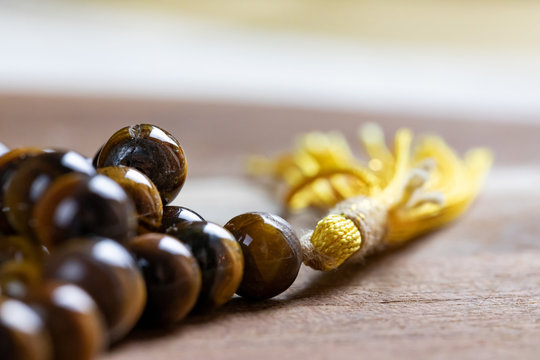 Close up of a holy Mala prayer beads necklace made of tiger eye gem stones with a yellow tassel promoting mediation healing and peace