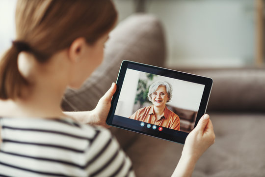 Young woman having video call with eldery mother on tablet