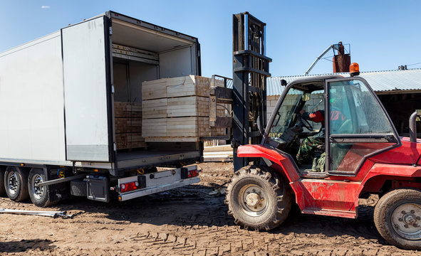 The machine loads the boards, lumber from the finished goods warehouse onto the truck