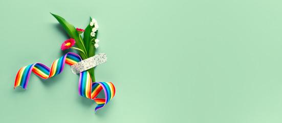 Thank you doctors and nurses! Rainbow ribbon and bouquet of red primrose and lily of the valley flowers attached with medical aid patch. Creative panoramic flat lay on green background, text space.