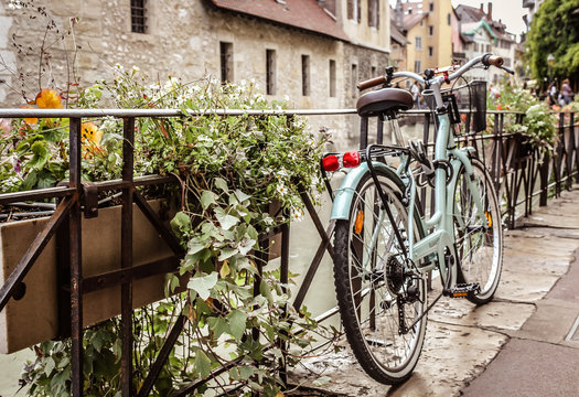 """Old bicycle parked near the Palais de l'Ile on the Annecy old town. The Palace, often described as a """"house in the shape of a ship"""" has been a prison, a courthouse and an administrative centre, France"""