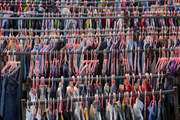 Huge selection of different used clothes for men, women and children on the rack in a second hand shop or thrift store. Concept of waste problem in fashion industry. Wall mural