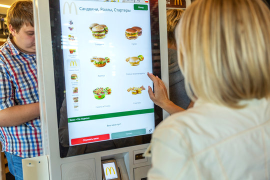 Moscow, Russia, 08/11/2019: A woman chooses food at McDonald's in the electronic menu.