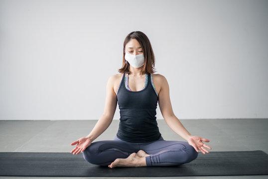 Yoga woman wearing medical face mask.