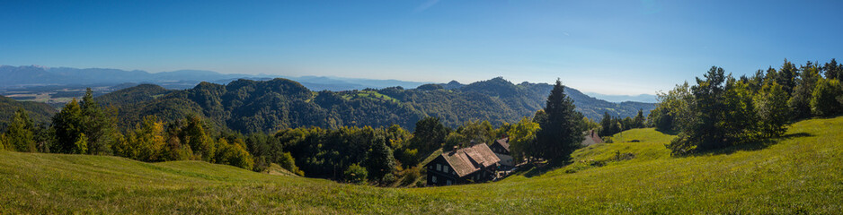 Panorama of a lonely farm with mountain hut on an open field in the hills or mountains of Govejk in Slovenia. Valley with forest and blue skies.
