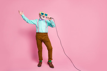 Full size photo of funny stylish grandpa holding karaoke microphone singing party songs chilling wear cool specs shirt suspenders bow tie pants socks isolated pink pastel color background