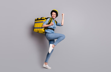 Full body photo crazy ecstatic girl courier deliver all quarantine covid-19 offer raise fists scream carry thermo container package wear denim jeans shirt helmet isolated gray color background Wall mural