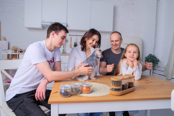 Foto auf AluDibond Kochen family with a dog plays in the kitchen light