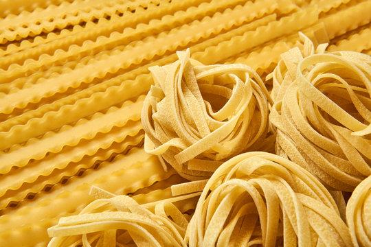 background of dried pasta, tagliatelle and mafaldini