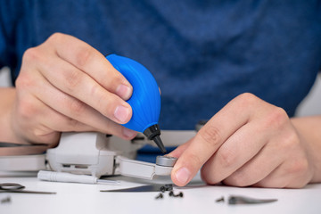 Man maintains drone using silicone dust blower cleaner tool for digital camera lens and other plastic or glass surfaces at a table Wall mural