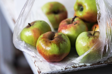 fresh apples in a plastic bag on a white wooden table