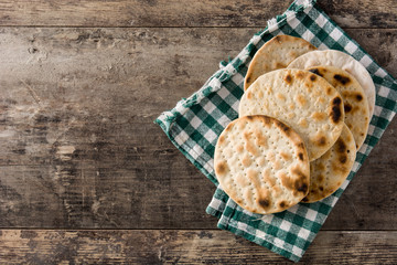 Handmade matzah for Jewish Passover on wooden table. Copy space