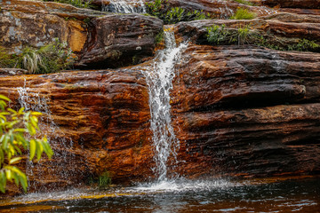 Close up of a small waterfall over red and black rocks into a pool, Biribiri State Park, Minas Gerais, Brazil