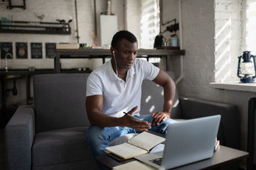 Serious ethnic man having online lesson at home