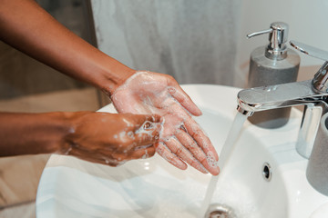 Cropped view of african american woman washing hands with soap in bathroom