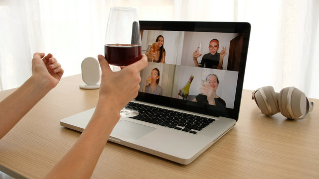 Crop female sitting with glass of wine at table and making video call via laptop with girlfriends while having remote party during coronavirus outbreak