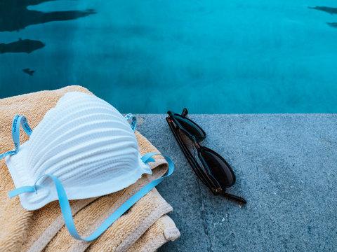 Medical face mask for protection against the Corona Virus (COVID-19) laying beside a pool