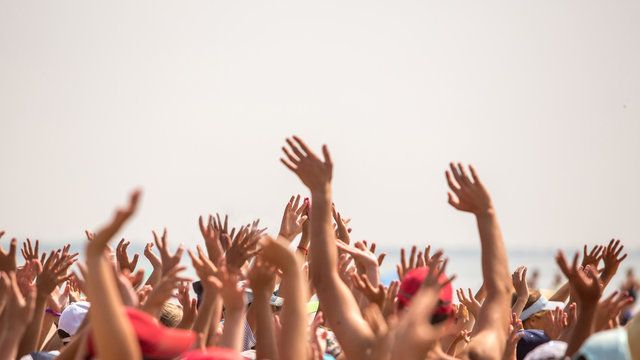 group of happy young people with hands up to the sky