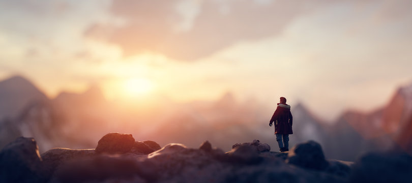 Man on the peak of mountain looking at sunset sky. Trip and adventure. Inspirational.