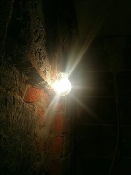 Illuminated Light Bulb Hanging Against Brick Wall