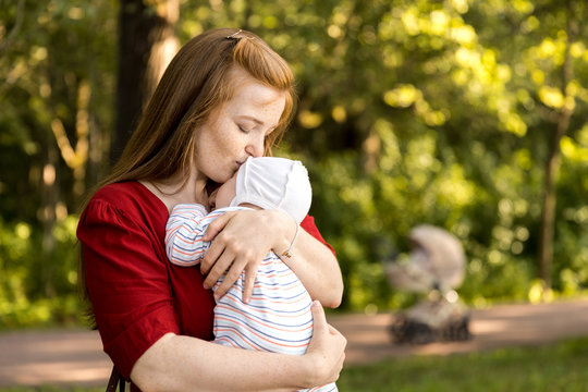 A young mother with a small newborn in her arms in a summer park. Happiness Maternity, Recovery Postpartum Concept