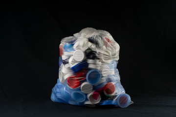 Big transparent bag filled with plastic bottle caps for recycling. Recycling, solidarity and no plastic concept. Recycling of plastic caps and take care of the environment.