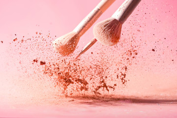 Make up brushes with powder splashes isolated on pink background