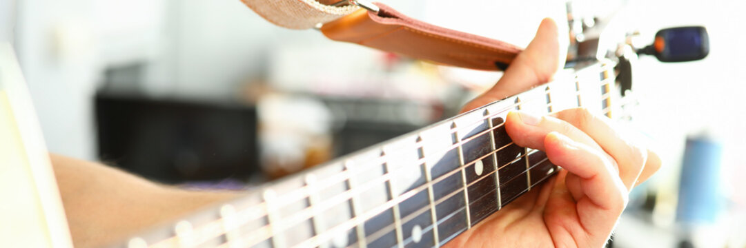 Man plays guitar, male hand holds neck guitar